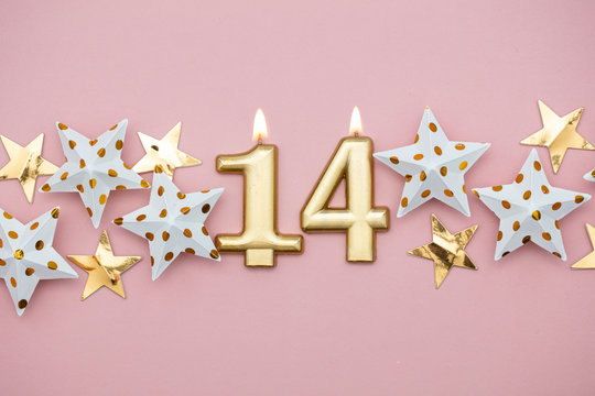 Number 14 gold candle and stars on a pastel pink background