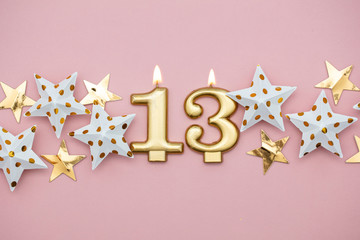 Number 13 gold candle and stars on a pastel pink background