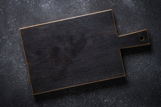 Black wooden cutting board on black stone table.