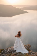 Back aerial view of beautiful bride in gorgeous white wedding dress standing on the edge of the cliff near the lake with islands. Scenic landscape view, Sunset