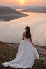 Rear view of beautiful bride in gorgeous white wedding dress standing on the edge of the cliff near the lake with islands. Scenic landscape view, Sunset