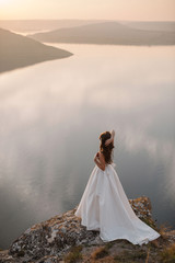 Rear aerial view of beautiful bride in gorgeous white wedding dress standing on the edge of the cliff near big lake with islands. Scenic landscape view, Sunset