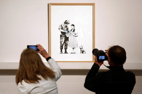 """An offset lithograph entitled """"Stop and Search"""" (2007) by British street artist Banksy is displayed before the opening of the urban art auction organized by Artcurial in Pari"""