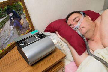 Man using CPAP Machine and Sleeping Mask for Treatment of Sleep Apnea