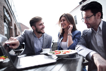 colleagues discuss new information at a table in a cafe