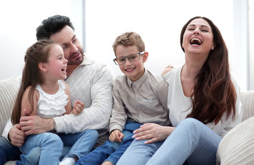 loving parents with children sitting on the couch
