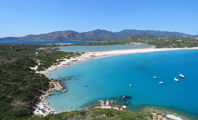 View from above over the white beach, tranquil bay, distant mountains and blue water of the Mediterranean Sea at Porto Giunco, Sardinia, Italy