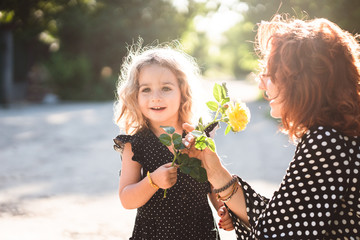 Mom and little daughter with a yellow rose