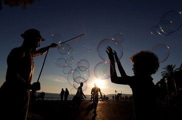 A street artist performs during a warm and sunny autumn day on the Promenade des Anglais in Nice