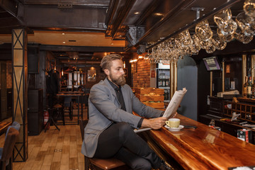 Young bearded businessman reading a newspaper