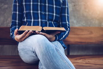 close up of man holding and read bible while sitting on wooden chair, Christian background