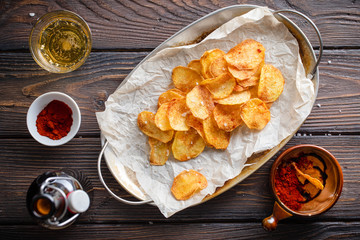 Homemade potato chips strewn with rock salt and paprika served with sous on a wooden rustic table with a bottle and glass of beer.