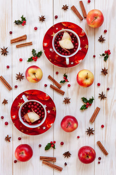 Two cups with hot Christmas fruit drink with spices and berries Christmas background with holly, red apples, cinnamon, anise and cranberries. Top view, close-up on white wooden table