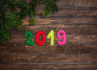 2019 made of felt and Christmas fir tree branch. Childish craft New year background on dark rustic wooden background. Holiday card - 2019 happy new year!