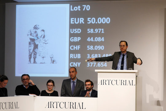 """Auctioneer Arnaud Oliveux reacts at the final price in the bidding of the offset lithograph entitled """"Stop and Search"""" (2007) by British street artist Banksy at the urban art auction organized by Artcurial in Paris"""