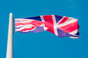 the flag of Great Britain flying in the wind against a blue sky
