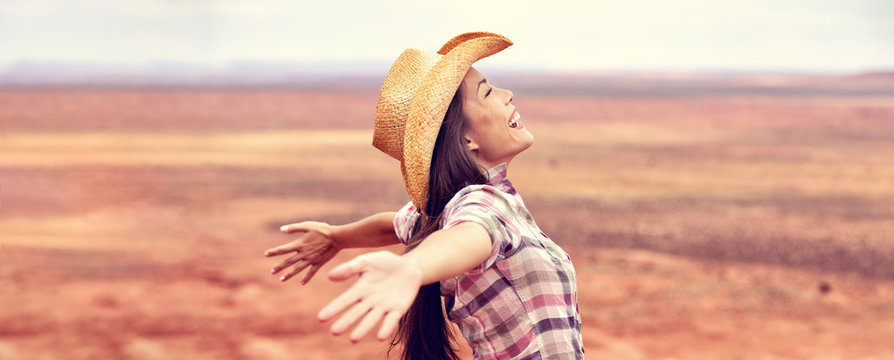 Cowgirl american woman happy with open arms in freedom wearing cowboy hat enjoying outback background panorama banner. Beautiful smiling multiracial Caucasian Asian young woman, Arizona Utah, USA.