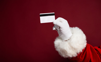 Male hand in white glove and Santa Clause costume holding credit card on red background, Christmas and New year concept– stock image