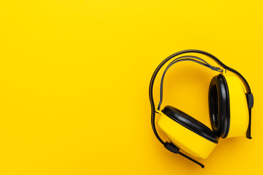 hearing protection industrial ear muffs on yellow background. top view of yellow protective ear muffs with copy space