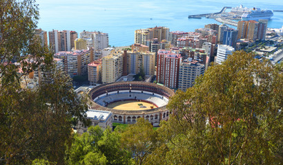 Malaga City Bull Ring Plaza de Toros      or La Malagueta  viewed from above with tower blocks harbour and the Ocean in background
