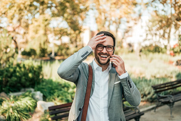 Handsome business man laughing while talking on the mobile phone outdoors.