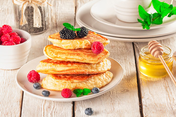 Delicious ready-made golden pancakes with fresh blueberries, raspberries and honey