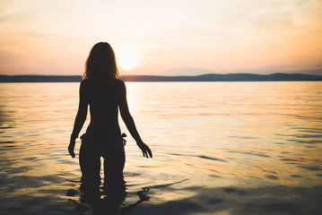 Young attractive girl model silhouette in the sea