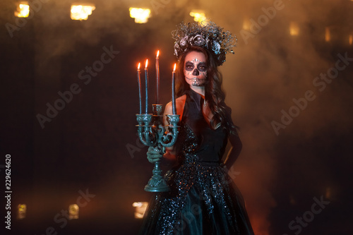 Portrait of a young woman with make-up for Halloween. She stands in the dark, holding a candlestick with burning candles.