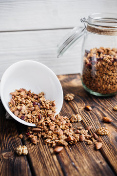 homemade granola in glass jar and scattered on a wooden table.