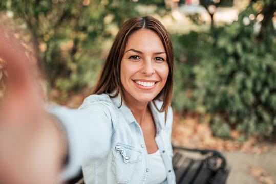 Beautiful girl taking selfie in the park.