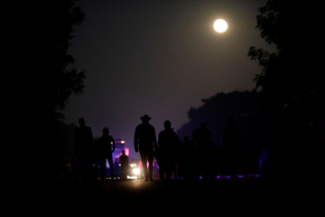 Migrants, part of a caravan of thousands from Central America en route to the United States, make their way at dawn to Mapastepec from Huixtla