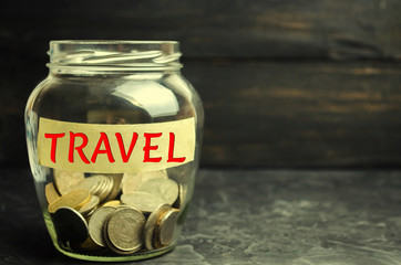 "Glass jar with coins and the inscription ""travel"". concept of saving and collecting money on travel. Budget for vacation and resort. accumulation savings plan. copy space"