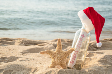 Christmas Santa hat on Seasons Greetings message in a bottle with starfish in beach sand and water background
