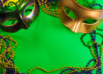 Wall Mural - Two Mardi Gras mask with colorful beads on a green background