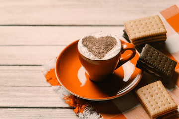 photo of the cup of coffee and cookies on the tablecloth on the white wooden background