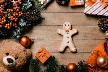 photo of the gingerbread man and christmas decorations on the brown wooden background