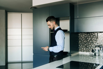 Stylish groom in white shirt and bow tie posing at window light. Confident and happy portrait of man. Groom getting ready in morning. Creative wedding photo