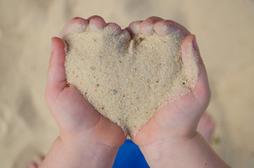 Child's hand holding sand in the shape of a heart, summer, love concept