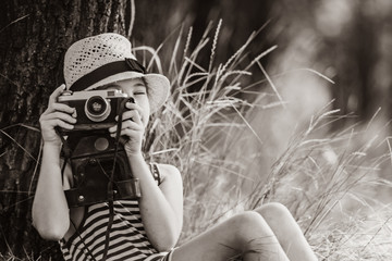 photo of the beautiful girl taking photos with her camera near the tree . Image in black and white color style
