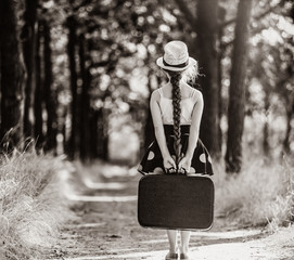 photo of the beautiful girl with suitcase on the countryside road . Image in black and white color style