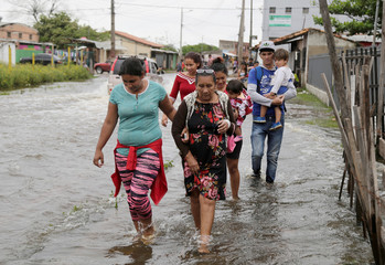 People walk through a flooded street on the outskirts of Asuncion