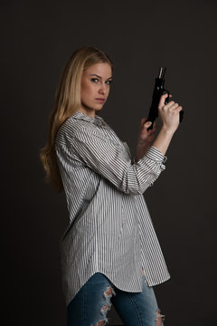 young dangerous blond woman with a gun