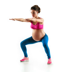 Sporty pregnant girl squatting, doing sit-ups isolated on white background. Concept of healthy life