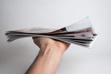 Mann hält ein Magazin oder Zeitschrift in der Hand