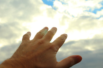 Male hand reaching for the sky. Close-up. Background.