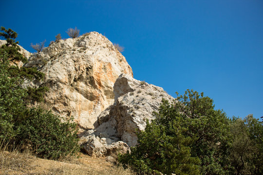 south dry rocks mountains and green plants on blue colorful sky background, good place for hiking, Greece, Thermopylae