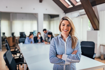 Portrait of a smiling attractive businesswoman with crossed arms in a meeting room.