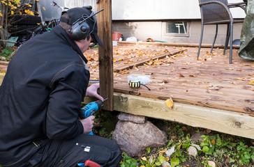 A man builds a wooden flooring. Master works battery screwdriver.