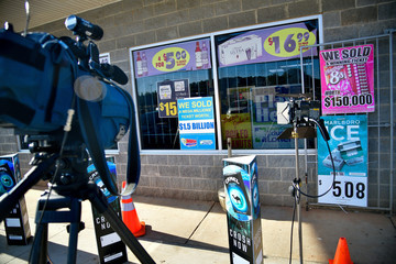 TV cameras point towards signs announcing the purchase of the winning Mega Millions ticket at the KC Mart in Simpsonville
