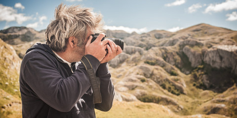 Professional photographer take picture of landscape at the mountain peaks